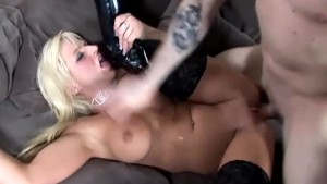 Sex on a couch in shiny black boots over stockings