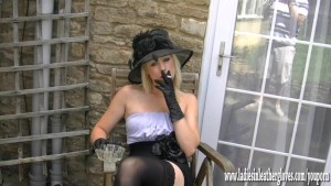 Sexy blonde smoking seductively flashing pussy in leather gloves and nylons