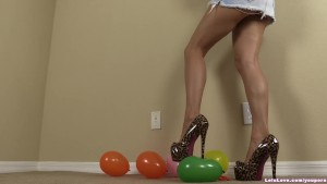 Girl with long legs upskirt pussy peeks popping balloons with heels