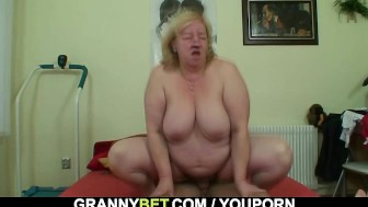 Grandma with huge melons enjoys riding his young cock